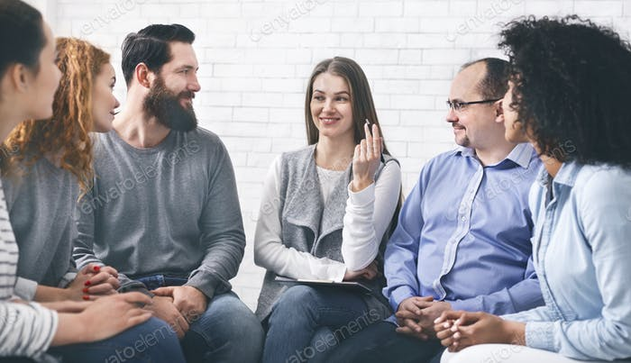 Smiling Psychologist Talking To Group Members At Therapy Session In Rehab