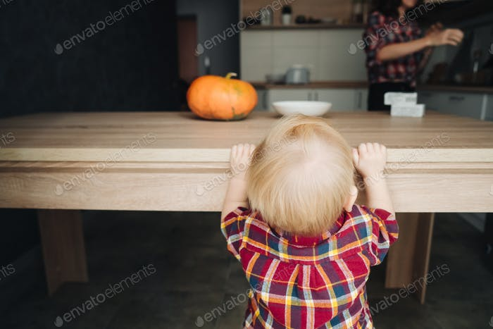 little boy is standing by the table