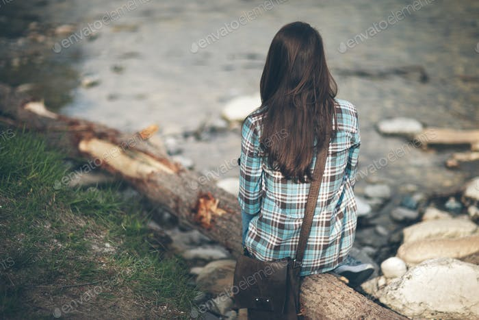 Young woman sitting along the river