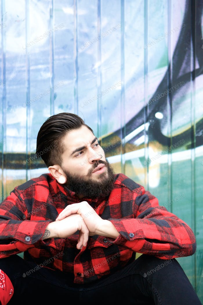Cool guy with beard and piercings sitting outdoors