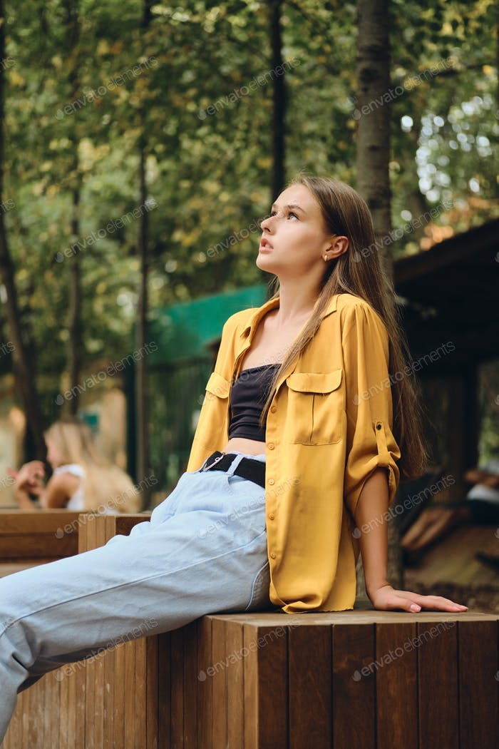 Beautiful teenage girl in yellow shirt thoughtfully looking aside sitting on wooden bench in park