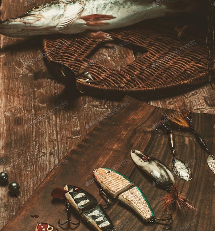 Рыболовные инструменты и свежая щука на деревянном столе