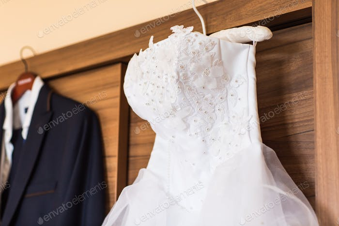 The perfect wedding dress on a hanger in room of  bride