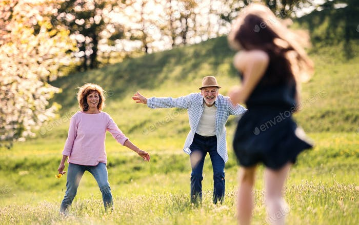A small girl with grandparents running outside in spring nature.