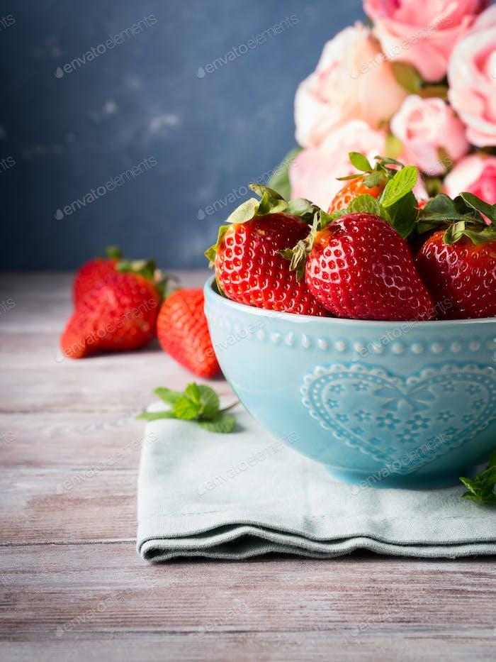 Erdbeeren in Schüssel mit Herz und Rosen