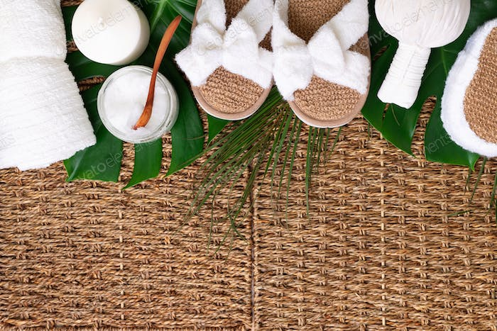 Spa tools: white towel, bamboo slippers, herbal ball, cream, wooden brush, coconut oil, monstera on