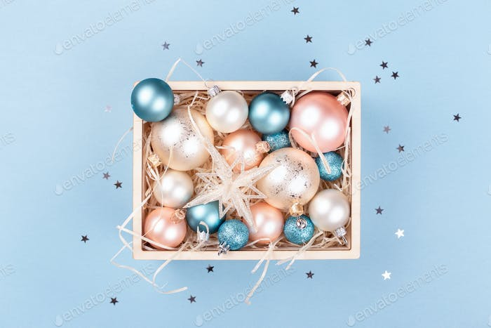 Wooden Box with Christmas Decorations on Blue Background.