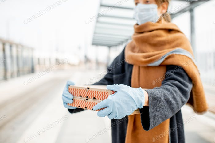 Woman in medical mask and gloves with takeaway food outdoors