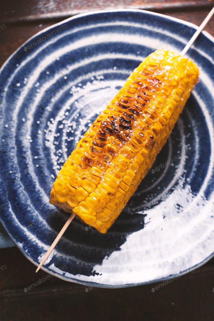 Roasted corn with salt on blue plate closeup