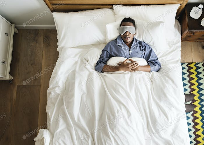 Black man sleeping on bed with eye mask