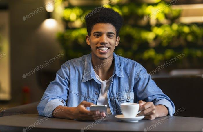 fröhlich schwarz teen Kerl trinken Kaffee bei cafeteria