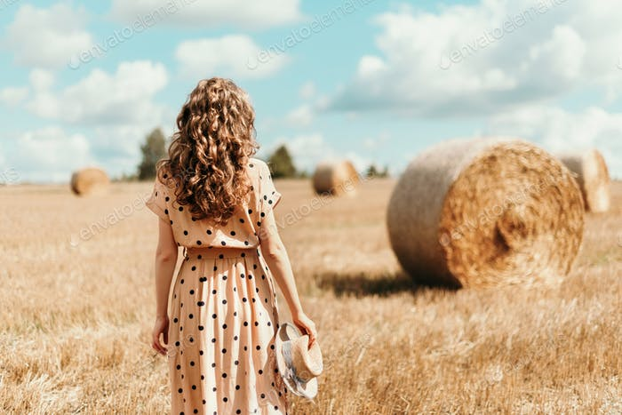 Young woman standing on harvested field with straw bales. Agriculture background with copy space