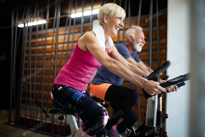 Happy senior people doing indoor biking in a fitness club