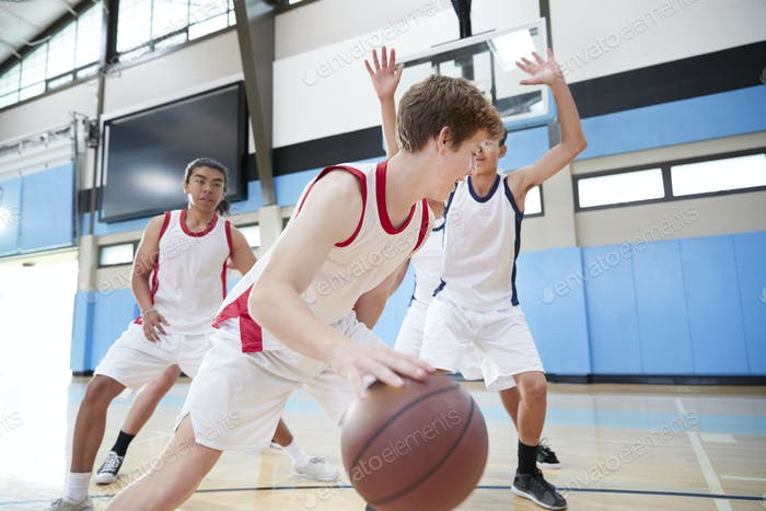 Male High School Basketball Team Dribbling Ball On Court
