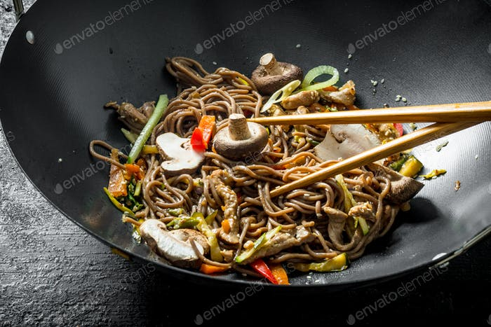 Hot soba noodles in a wok pan with mushrooms, sauce and beef.