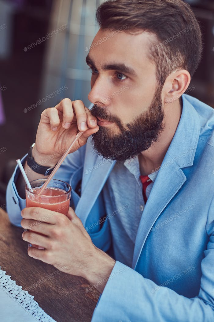 Fashionable bearded male with a stylish haircut sitting in a cafe outdoors.