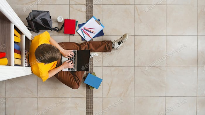 Young male student sitting at bookshelf and using laptop