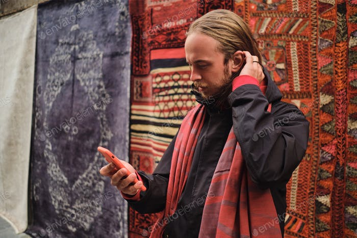 Young attractive man intently using smartphone during walk through local market