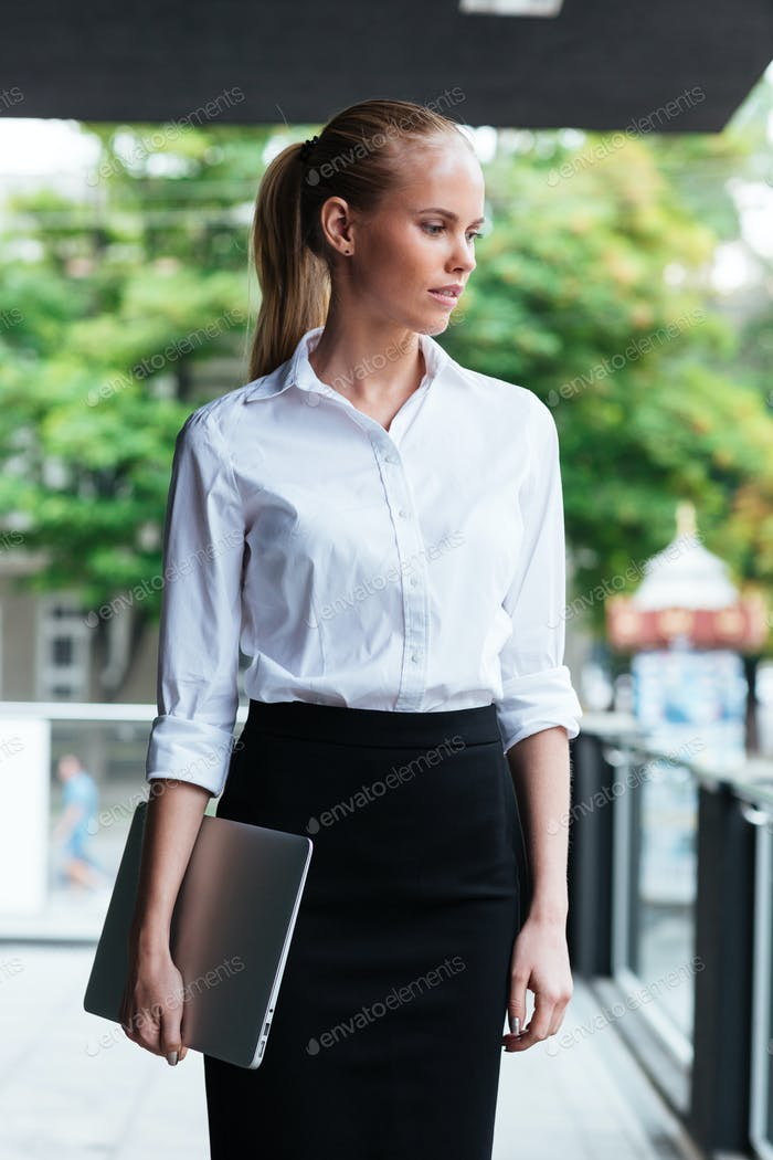 Smart business woman with laptop standing at the glass balcony