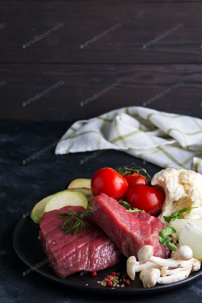 Raw beef steak on the bone with fresh vegetables in a grill pan on a concrete background, top view