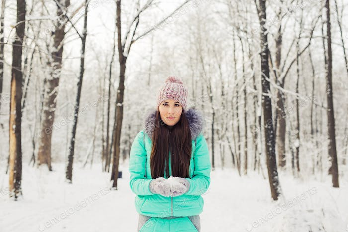 Girl in winter snowy park. Snow, cold and seasonal concept