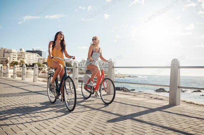 Weibliche Freunde fahren ihre Fahrräder auf der Promenade