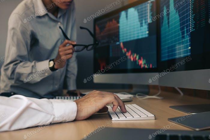 Empresarios discutiendo y analizando con ganancias bursátiles en la computadora en la sala de oficinas.