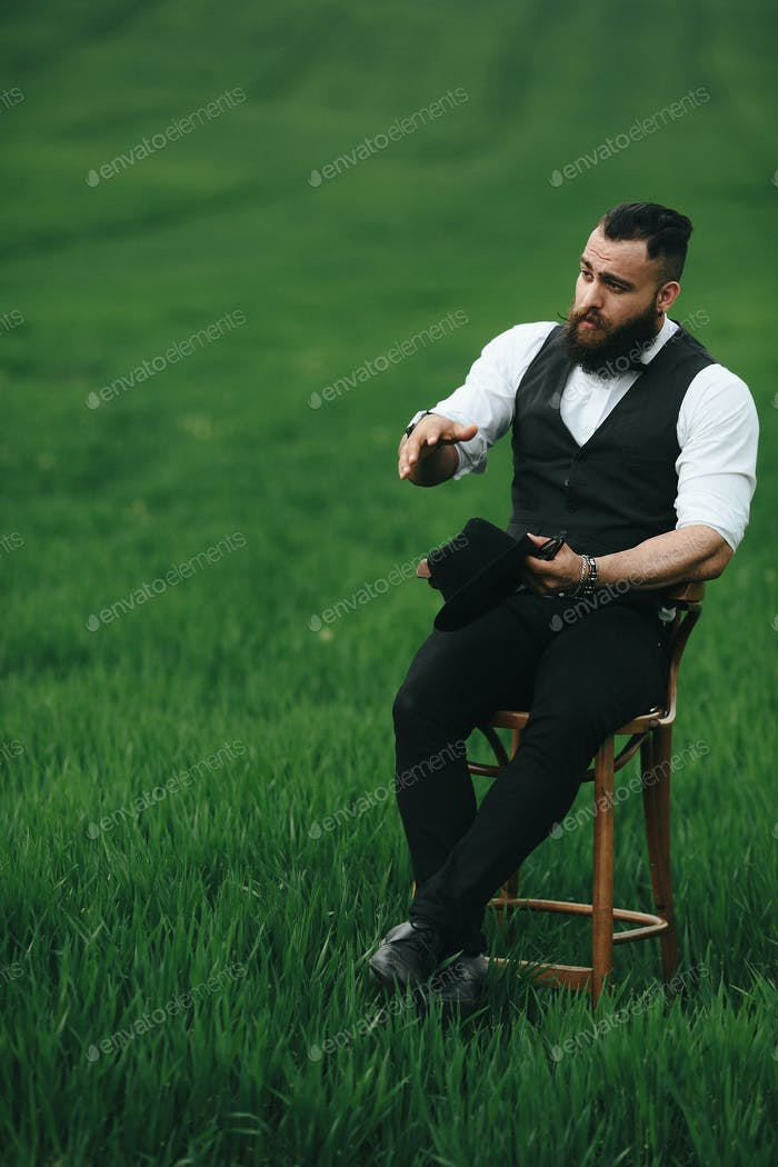 A man with a beard, thinking in a field near chair