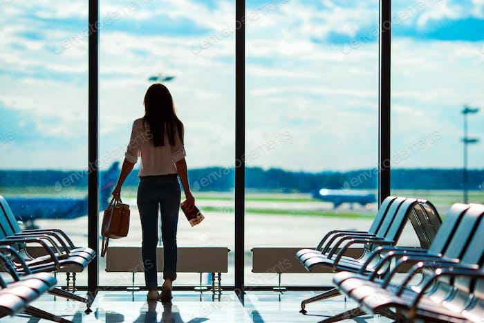 Junge Frau am internationalen Flughafen mit ihrem Gepäck Hintergrund großes Fenster. Fluggast in einem