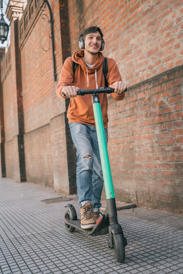 Young man driving electric scooter.