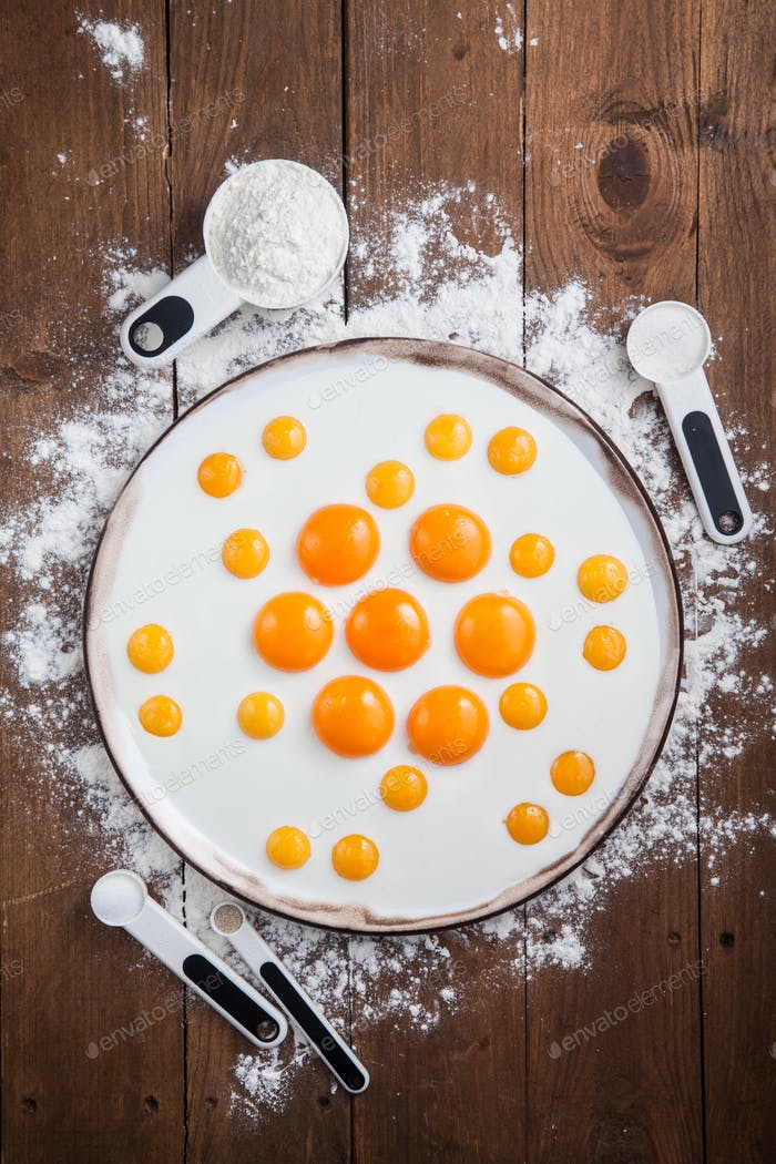 Bakery ingredients - flour, eggs, butter, sugar, yolk. Flat lay, top view.