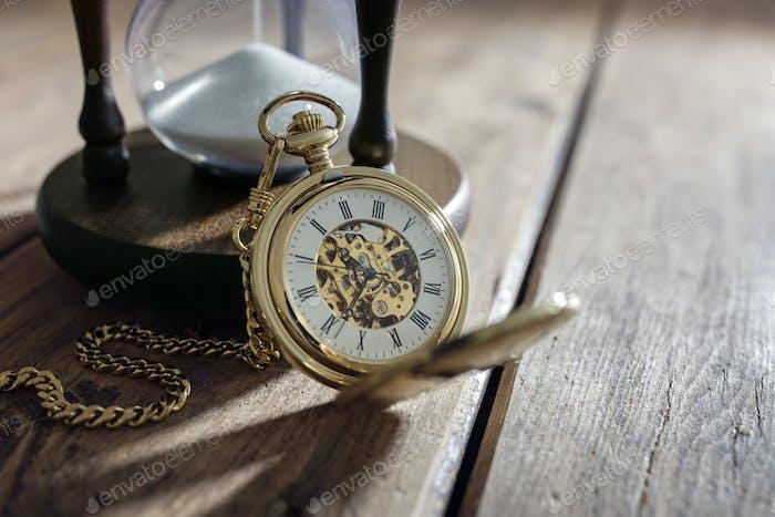 Goldene Taschenuhr und Sanduhr