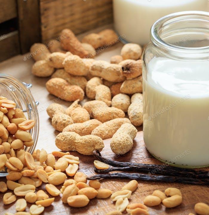 Erdnussmilch auf einem Holztisch. Nüsse und Glas mit Milch, Milchmilch für Veganer und Vegetarier