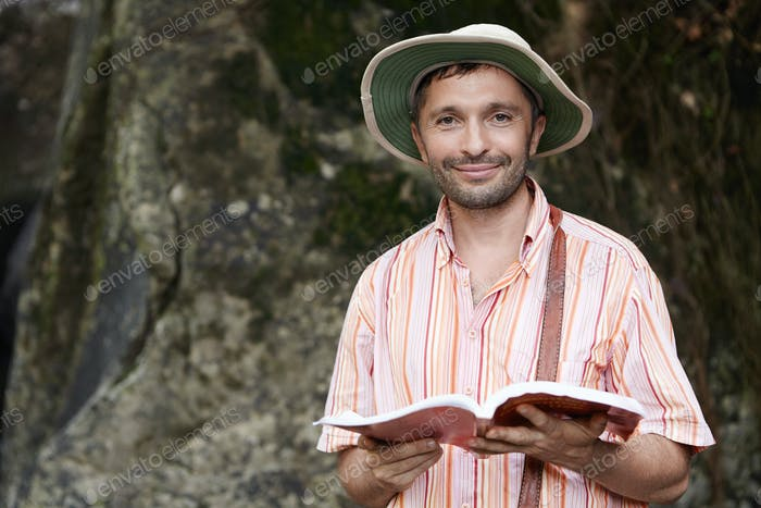 Portrait of male botanist or biologist with stubble wearing panama hat and striped shirt at field wo