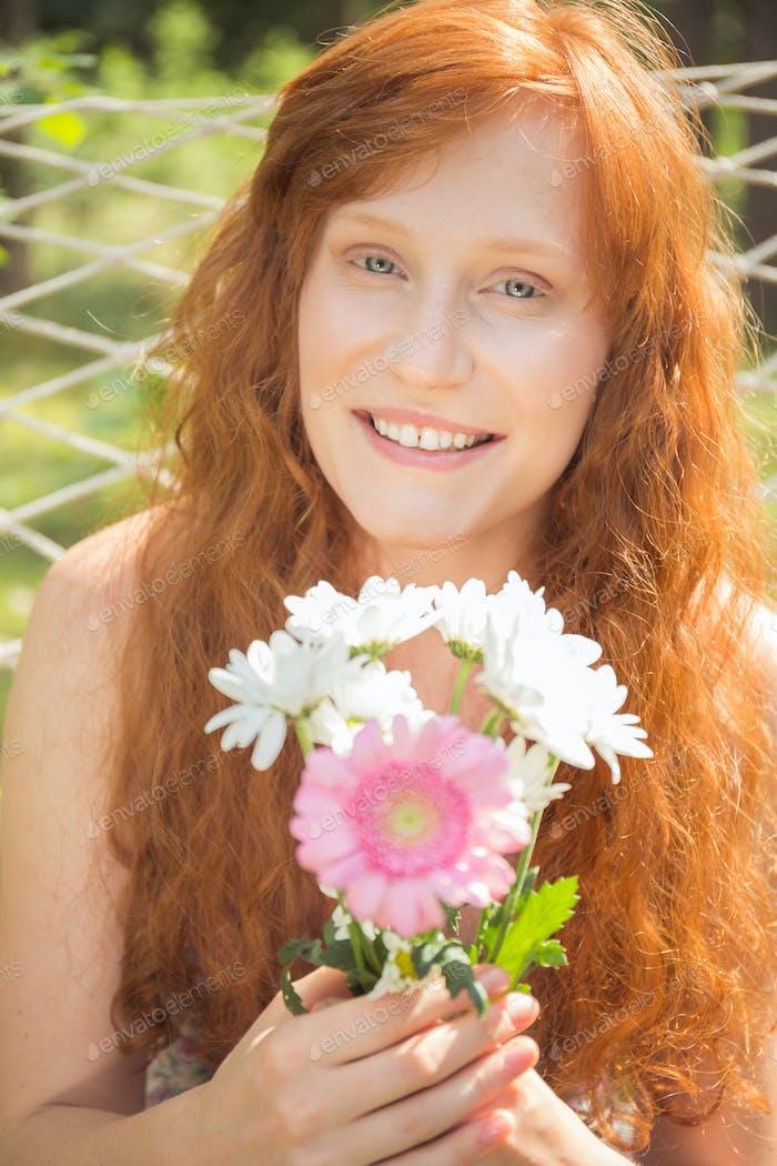 Ginger girl holding field flowers