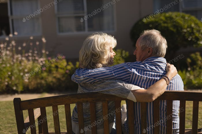 Rear view of senior Caucasian couple embracing each other in the park