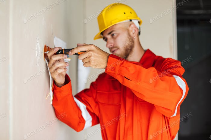 Young builder in orange work clothes and yellow hardhat thoughtf