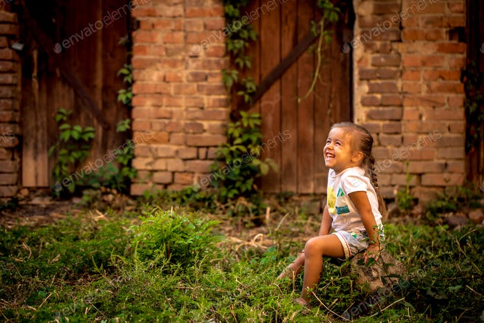 beautiful little girl playing near abandoned buildings and old doors