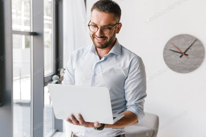 Cheerful adult office man wearing white shirt expressing success