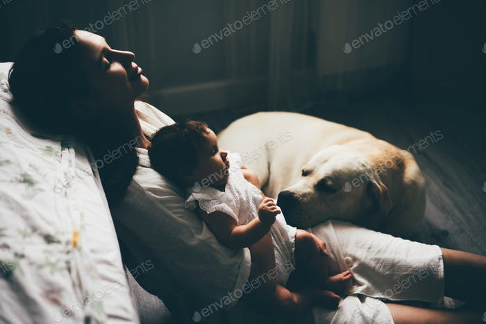 Mutter mit einem Baby Mädchen und einem niedlichen Labrador zu Hause