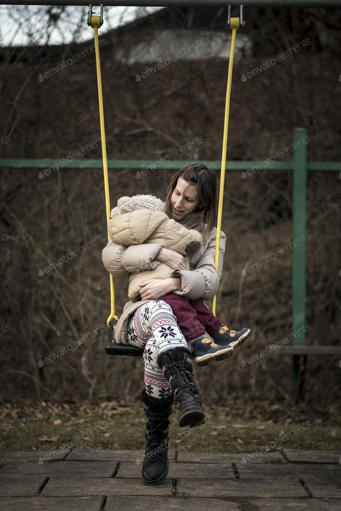 Mother enjoying on a swing in a park with her toddler in her lap
