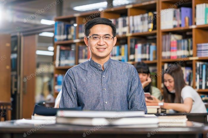 Porträt eines asiatischen Lehrers in der Bibliothek und im Klassenzimmer, Universitätsbildung, zurück in die Schule