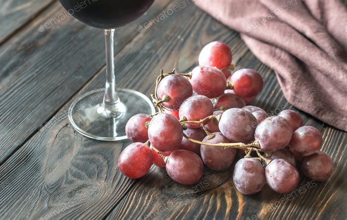 Glass of red wine with bunch of red grape