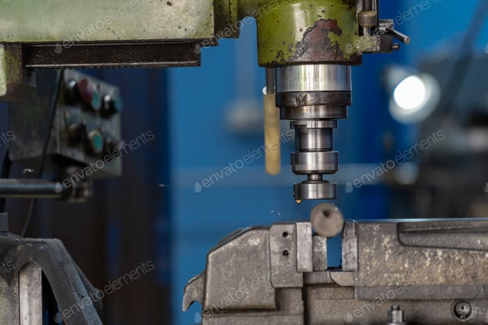 Professional machinist hand working with milling machine in metalworking factory
