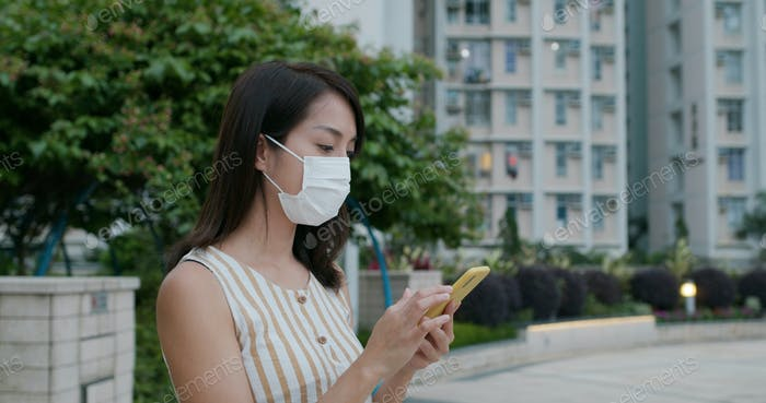 Woman wear face mask and use of mobile phone at outdoor