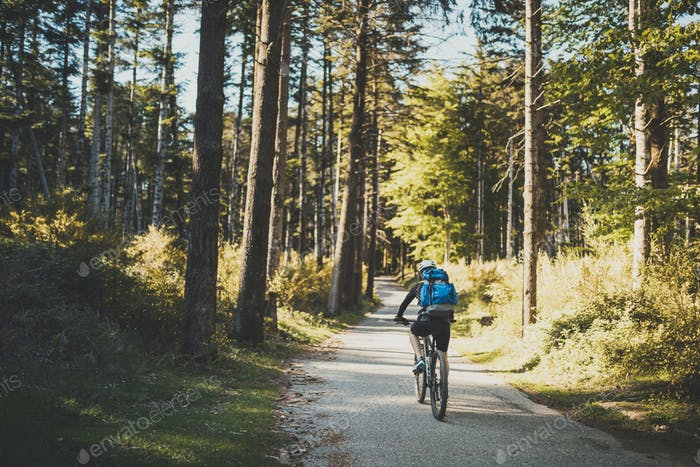 Young boy with bicycle and backpack in the mountains. Mountainbike excursion