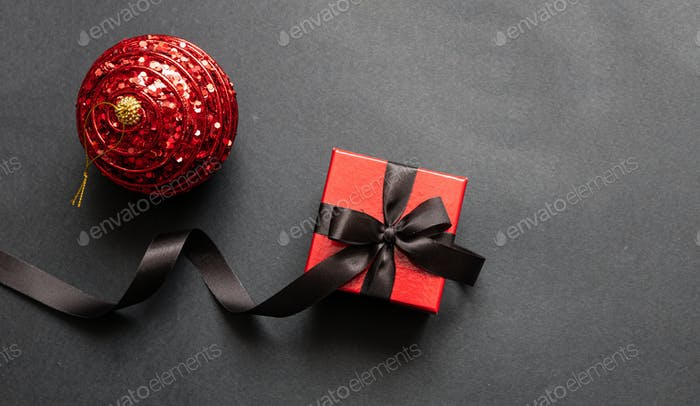 Christmas present and red xmas ball against black background, Black Friday Christmas concept.