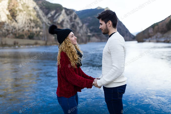 Beautiful young couple in love over winter background.