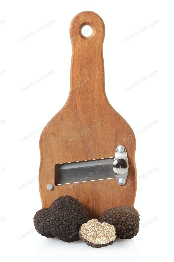 Black truffles and wooden truffle slicer isolated on white