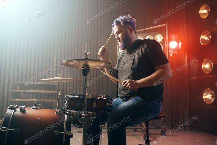 Bearded drummer with colorful hair, rock performer